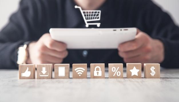Человек с помощью планшетного компьютера. деревянные кубики в столе. покупки в интернет магазине