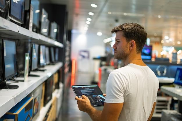 電器店で買い物中にタブレットを使用している男性