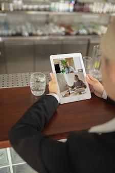 Человек, использующий планшет для видеозвонка, пьет воду