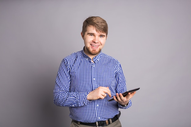 Man using tablet on gray wall.