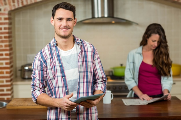 Man using tablet in kitchen while woman reading newspaper in background