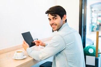 Man using tablet looking behind