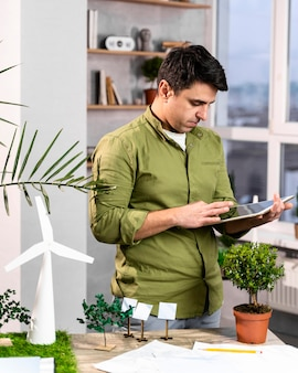 친환경 풍력 발전 프로젝트 레이아웃을 위해 태블릿을 사용하는 남자