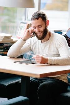 책상에 연필로 태블릿 pc를 사용하는 사람