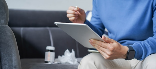 Man using tablet to video conference call with doctor for telemedicine