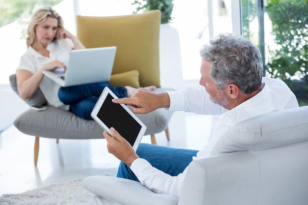 Человек используя таблетку пока женщина держа компьтер-книжку