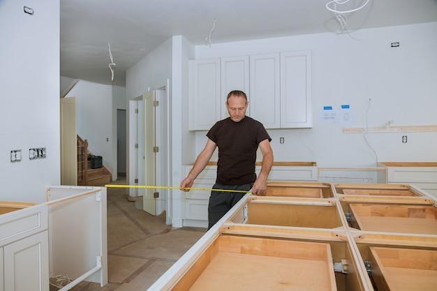 Человек используя рулетку для измерять на кухне внутри для улучшения дома.