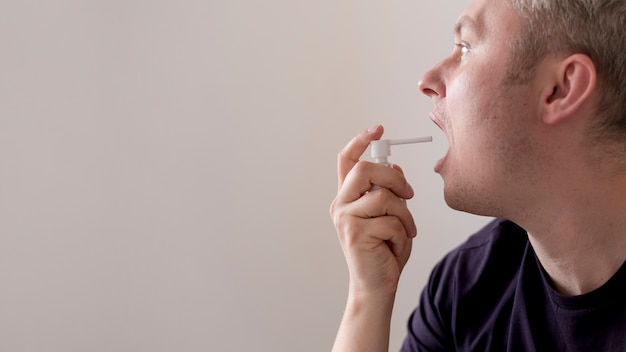 Man usingtreatment for sore throat copy space