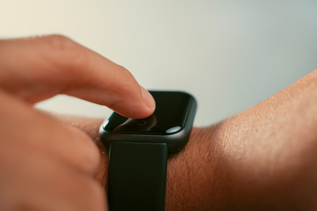 Man using trendy smart watches mobile app on touch screen