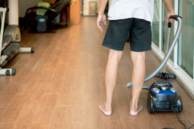 A man  using vacuum cleaner at home,cleaning floor