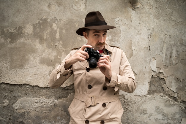 Man using vintage camera in a city street