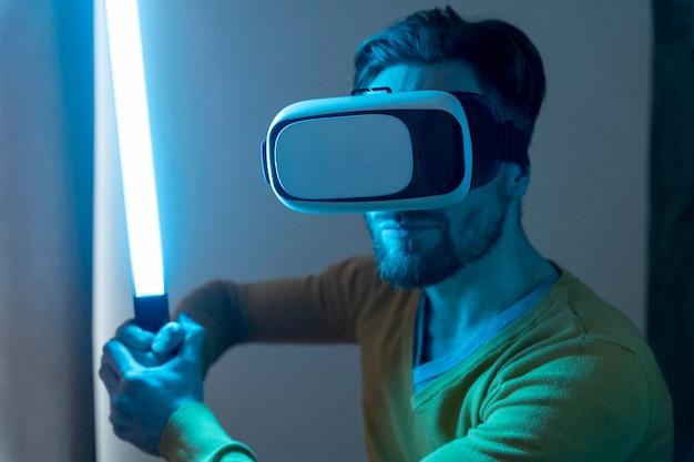 Человек, использующий гарнитуру виртуальной реальности и играющий с лазерным мечом