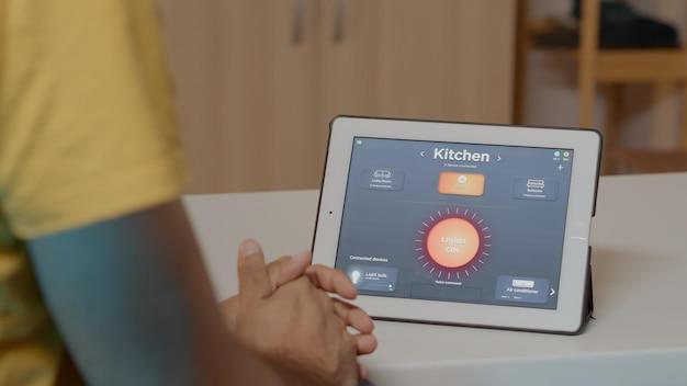 タブレットで音声起動のスマートワイヤレス照明アプリを使用している男性が、最新のソフトウェアを使用して社内の電球をオンにしています。未来の技術、音声起動コマンドでアンビエンスライトを制御する人