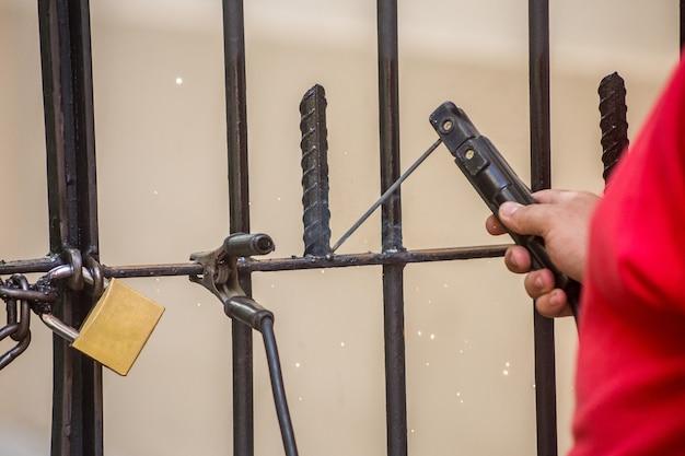 リオデジャネイロの屋外ゲートで鉄片を溶接する男性。