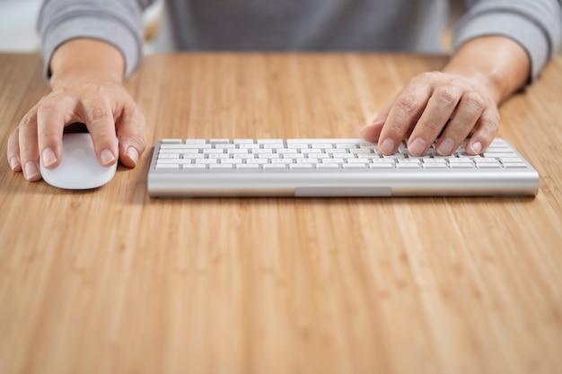 木製の机のテーブルに白いコンピューターのキーボードとマウスを使用している男。