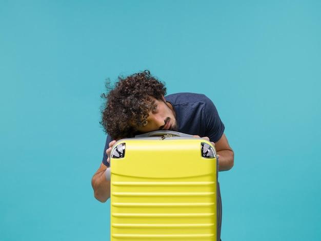 Uomo in vacanza in maglietta blu si sente stanco sul blu