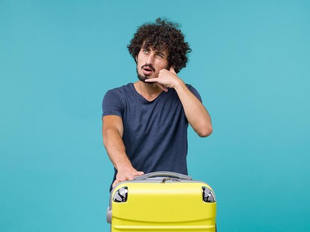 Uomo in vacanza in maglietta blu in posa sul blu