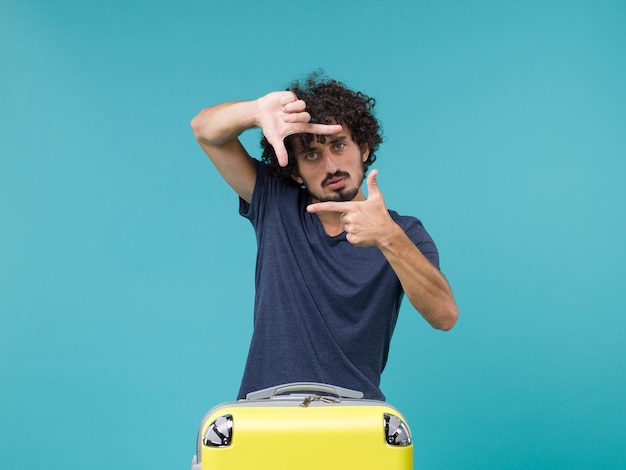 Uomo in vacanza in maglietta blu che mostra il segno della foto sul blu