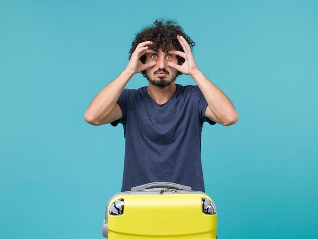 Uomo in vacanza in maglietta blu che apre ampiamente gli occhi sul blu