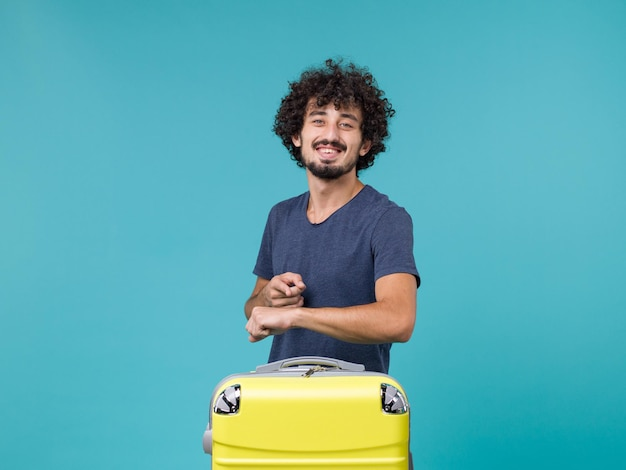 Man in vacation checking time and smiling on blue