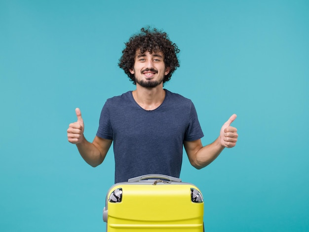 Uomo in vacanza in maglietta blu scuro sorridente sul blu