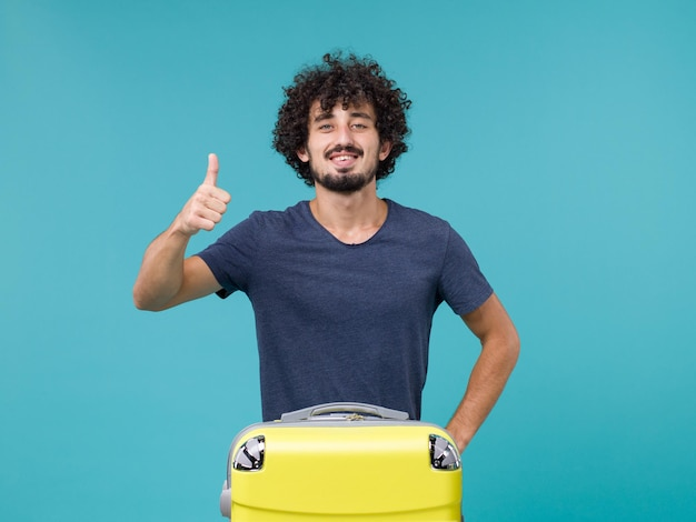 Man in vacation feeling happy and smiling on blue