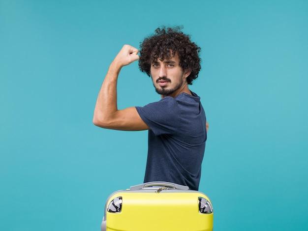 Uomo in vacanza che flette con valigia gialla su blue