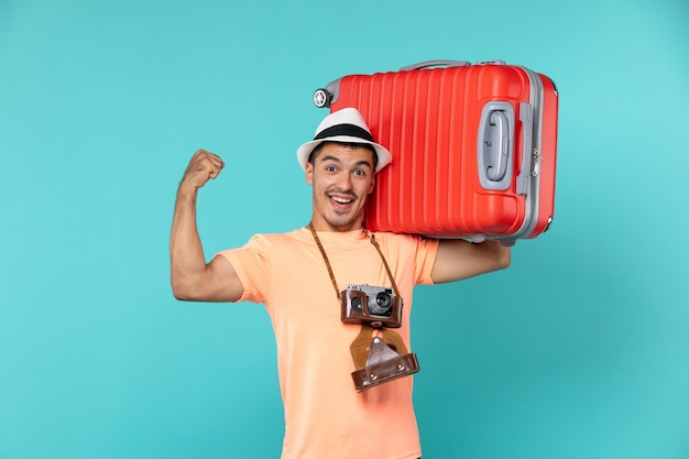 Man in vacation holding big red suitcase on blue