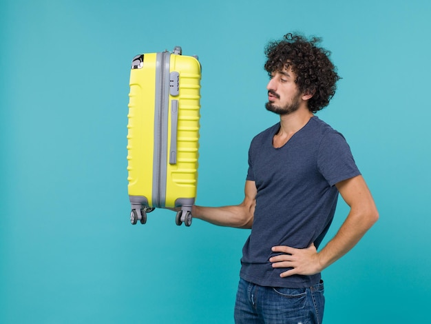Man in vacation holding big yellow suitcase on blue