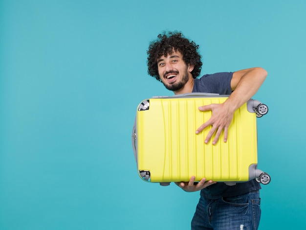 Man in vacation holding big yellow suitcase laughing on blue