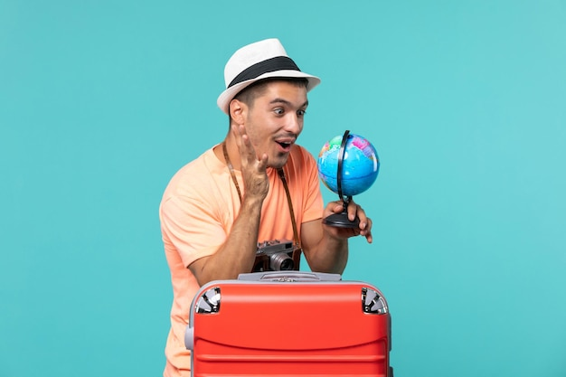 Man in vacation holding globe and taking photos with camera on blue