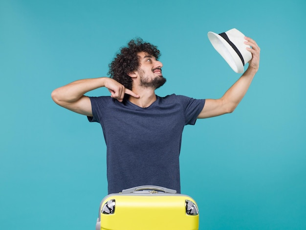 Man in vacation holding his hat on blue