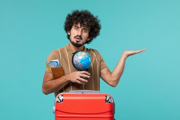 Uomo in vacanza che tiene un piccolo globo su blue