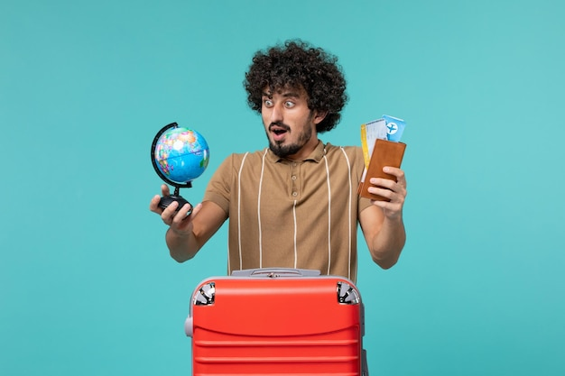 Man in vacation holding little globe and ticket on blue