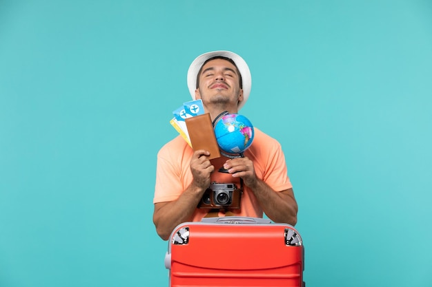 Man in vacation holding little globe and tickets on blue