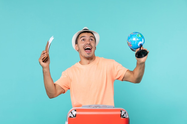 Man in vacation holding little globe and tickets on light-blue