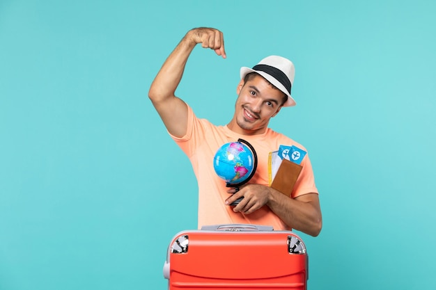 Man in vacation holding little globe and tickets on light blue