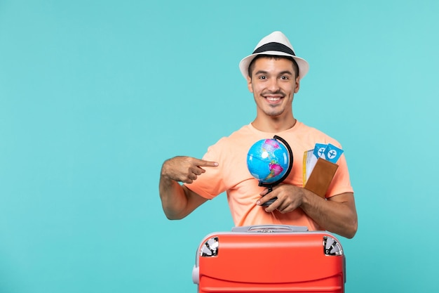 Man in vacation holding little globe and tickets smiling on blue