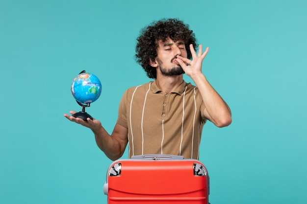 Man in vacation holding little globe with red bag on blue floor journey vacation plane trip sea voyage