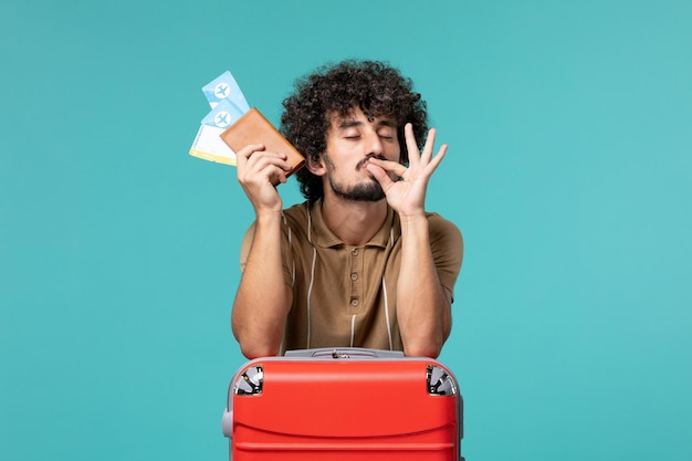 Man in vacation holding tickets and leaning to his red bag on blue