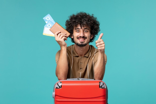 Man in vacation holding tickets on light-blue