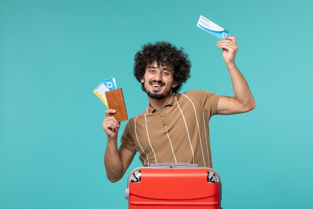 Man in vacation holding tickets and smiling on blue