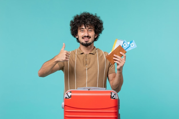 Man in vacation holding tickets and smiling on the blue
