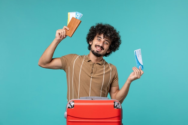 Man in vacation holding tickets smiling on blue