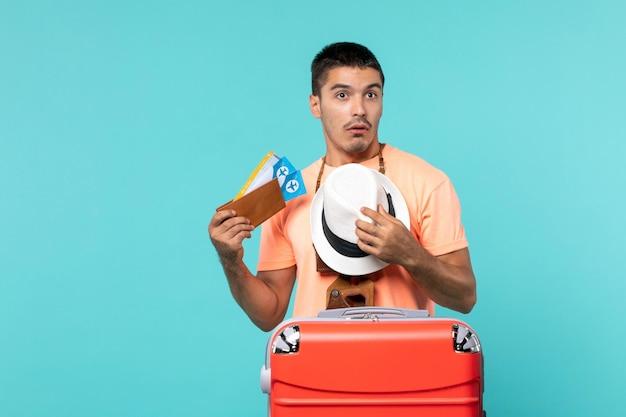 Uomo in vacanza in possesso di biglietti con borsa rossa sul pavimento blu viaggio vacanza viaggio viaggio aereo marittimo