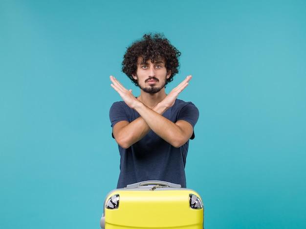 Uomo in vacanza che mostra segno di divieto su blue