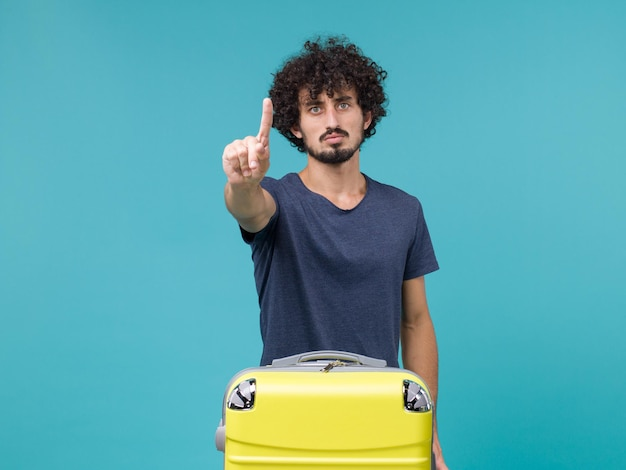 Man in vacation showing his finger on blue