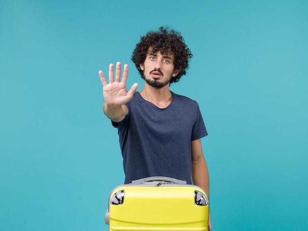 Uomo in vacanza che mostra il palmo sul blu on
