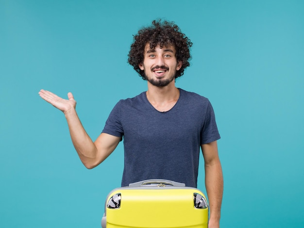 Man in vacation smiling on blue