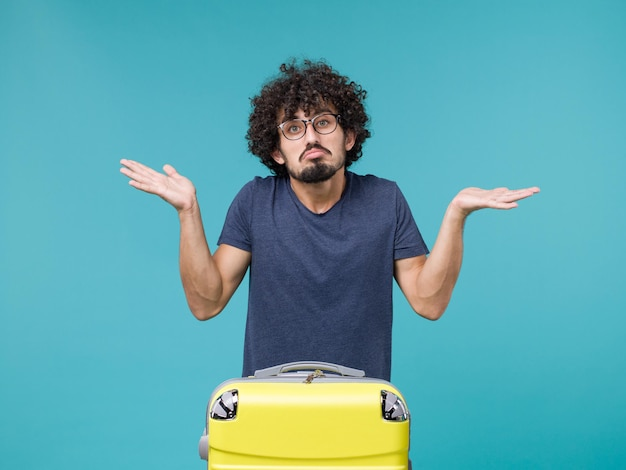 Man in vacation with big suitcase on blue